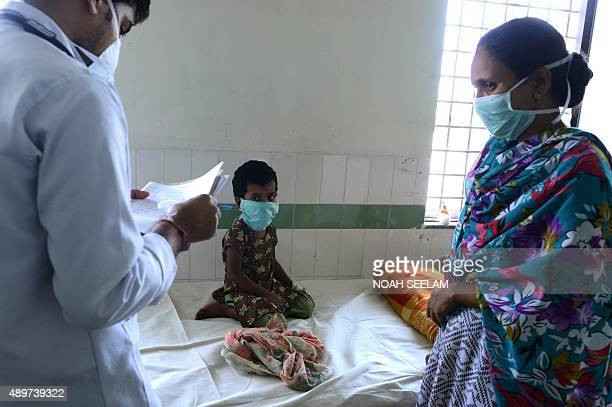 A young Indian patient looks on as a doctor examines his notes on a swine flu ward at The Gandhi Hospital in Hyderabad on September 24 2015 Five...