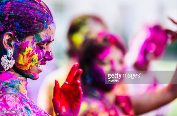 Young Indian people dancing and having fun, with their colorful faces and clothes, during the Holi Festival celebration in Jaipur India.