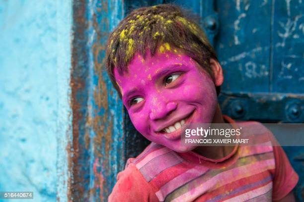 A young Indian reveller covered in coloured powder poses during the Lathmar Holi celebrations in the village of Barsana on March 17 2016 holi also...
