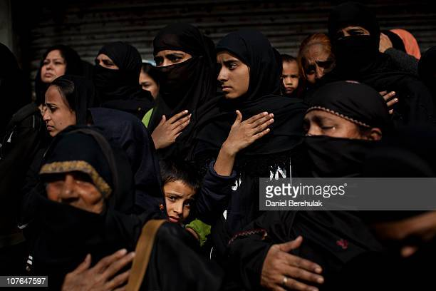 A young Indian Shiite Muslim boy looks on as Indian Shiite Muslim women mourn during a religious procession of the Ashura in New Delhi on December 17...