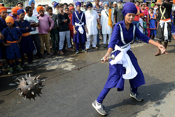 A young Indian Sikh devotee demonstrates her `Gatka` martial arts skills during a procession for the marriage anniversary of Guru Nanak Dev from the..