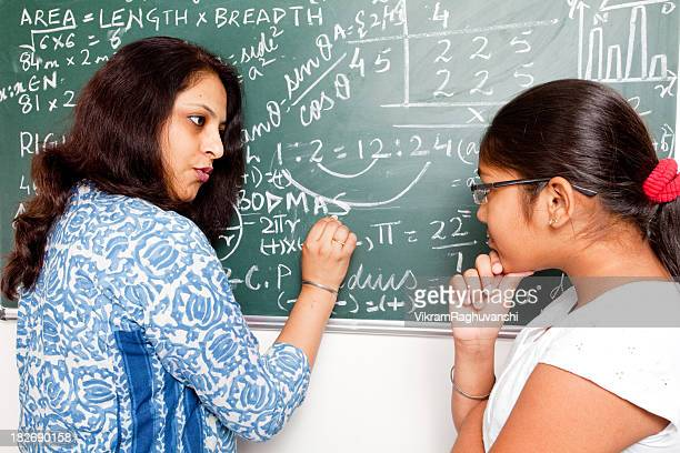 Young Indian Teacher explaining Mathematics problems to her student