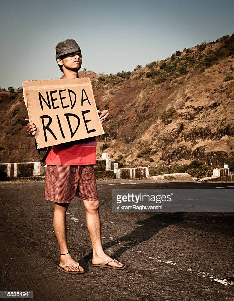 young indian tourist traveler man needs a ride hitch - hitchhiking stock pictures, royalty-free photos & images