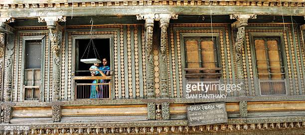 A young INdian woman holding an infant looks down from the window of a carved wooden house in the walled city surrounding the Hatkeshwar Mahadev...