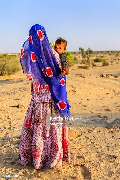Young Indian woman holding her baby, desert village, India