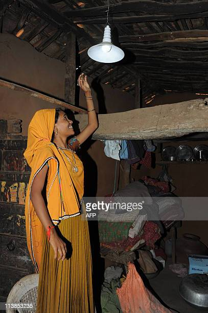 Young Indian woman Leelaben Bhagora reaches towards a lamp powered by solar electricity in her home in the remote hamlet of Nilwas in Banaskantha...