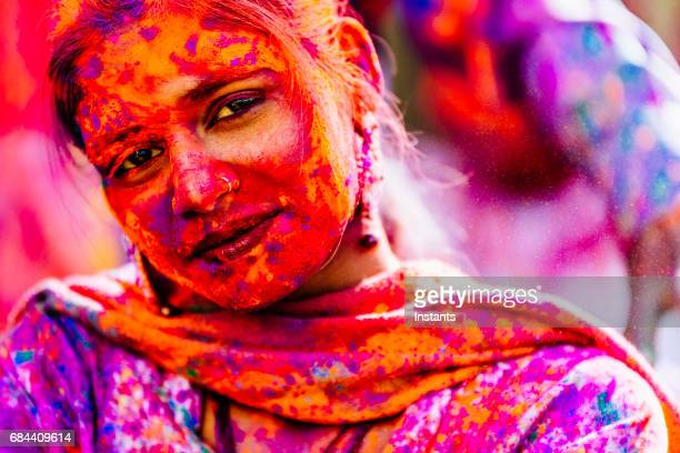 Young Indian woman, looking at the camera, during the celebration on Holi Festival in Jaipur.