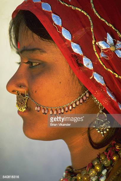 A young Indian woman of the nomadic tribes in the Great Thar Desert wears a nosering and decorative chain as part of her native dress in Pushkar...
