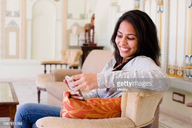 Young indian woman reading funny messages on mobile phone