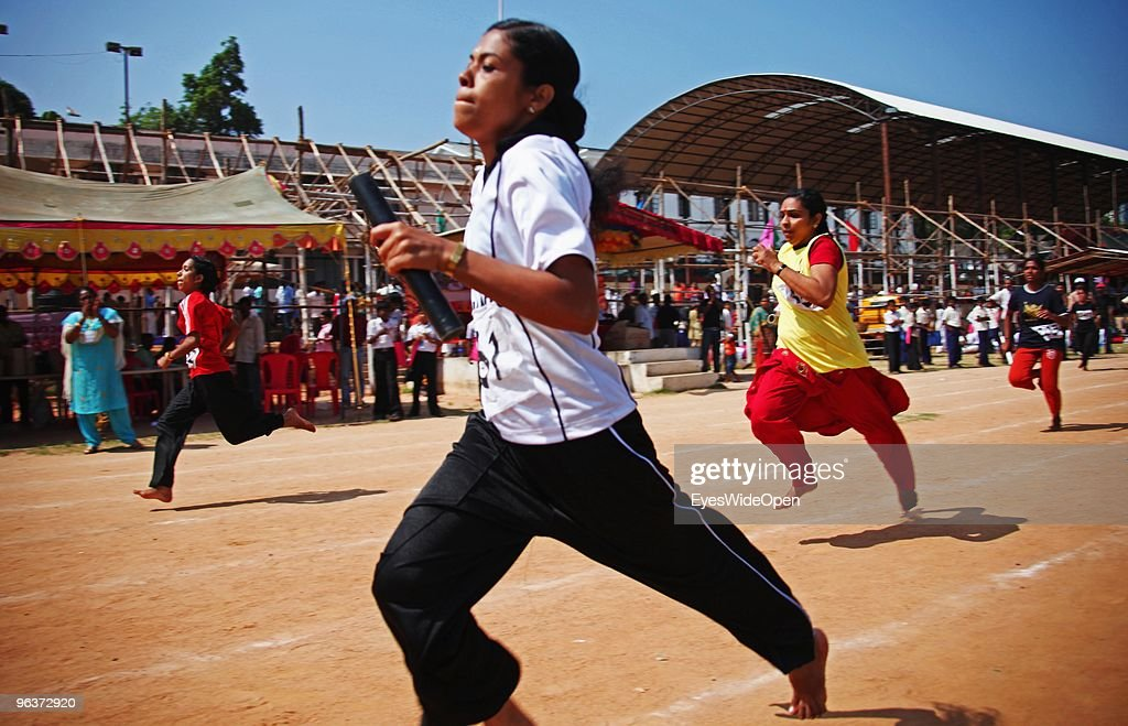 Young indian women are sprinting in a barefoot relay race, some are wearing the traditional long female salwar kameez dress, at a sports competition on January 15, 2010 in Trivandrum, Kerala, India.