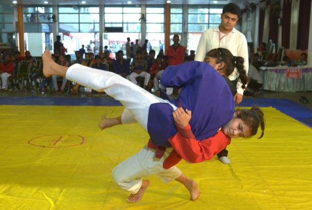 Young Indian women players are watched by a referee as they take part in a bout during The National Belt Wrestling and Goresh Championship in...