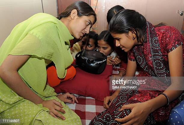 Young Indian women, some partially and some totally visually impaired applaud as they listen to radio commentary at The Andh Prakash Kanya Gruh...