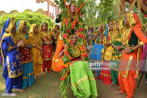Young Indian women wear traditional Punjabi dress as they dance the 'giddha' during Teej festival celebrations on the occasion of Sawan month at...