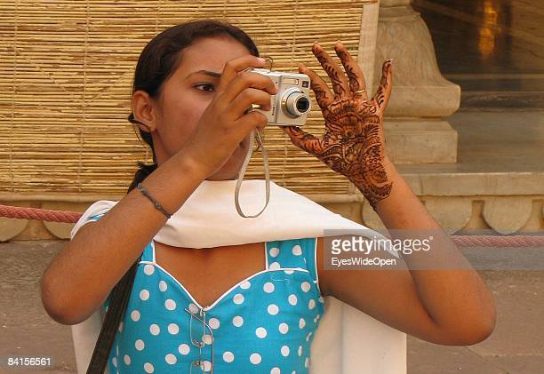 Young indian women with henna tattoo in her hands taking pictures with a digital camera in the City Palace in Jaipur India on January 08 2008
