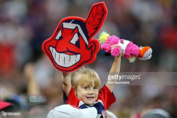 A young Indians fan in the stands holds up a foam Chief Wahoo and a Slider doll during the fifth inning of the Major League Baseball game between the...