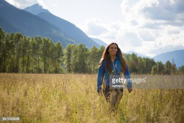 young indigenous canadian woman walking in a field - first nations stock pictures, royalty-free photos & images