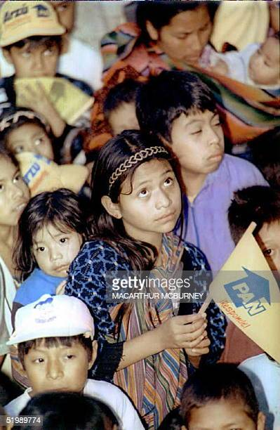 Young indigenous girl holding a flag from Guatemala's opposition conservative Party for National Advancement listens to a speech by PAN leader and...