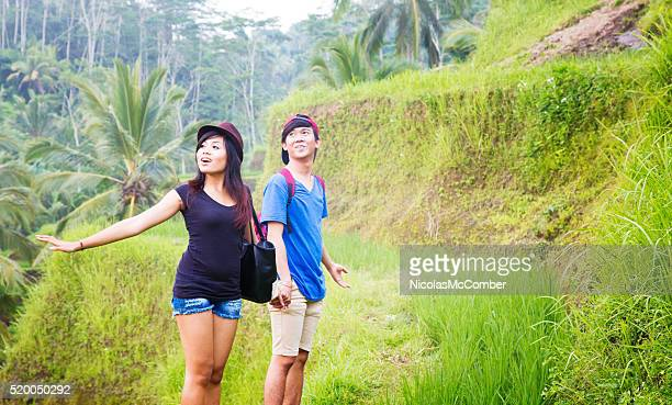Young Indonesian couple amazed at view visiting rice paddy