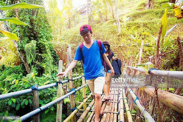 Young Indonesian couple crossing a bamboo bridge in jungle