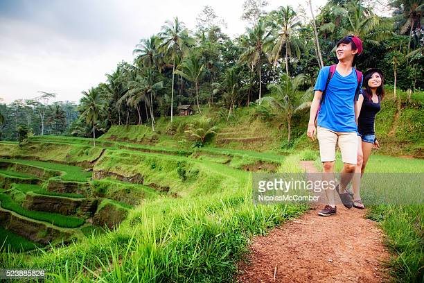 Young Indonesian couple visiting Bali terraced rice paddy