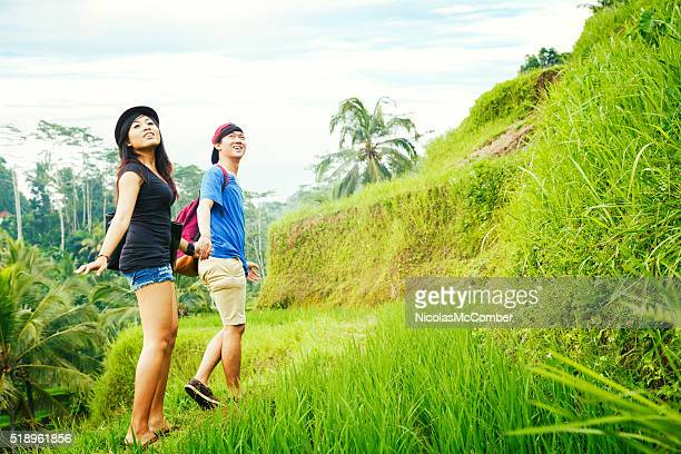 young Indonesian friends amazed at view while hiking in Bali