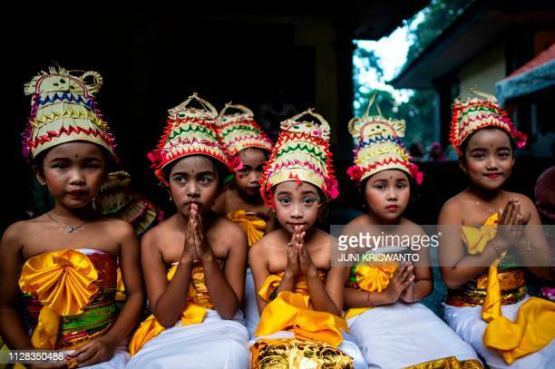 TOPSHOT Young Indonesian Hindu devotees offer prayers during the Melasti ceremony at Jolotundo temple in Penanggungan Mojokerto in East Java province...