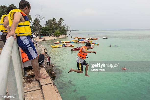 Young Indonesian man jumping from a bridge in Pulaua seribu just north Jakarta the capital city of Indonesia