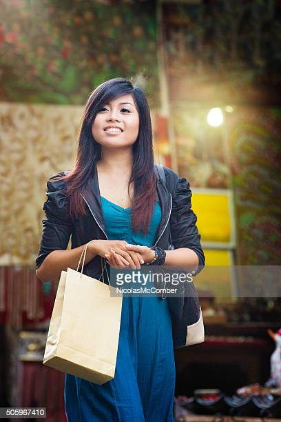 Young Indonesian woman  shopping for art at Ubud market