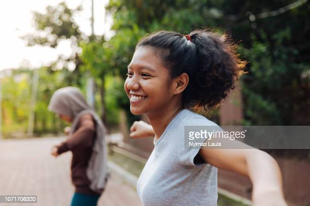 A young Indonesian woman with curly hair exercise