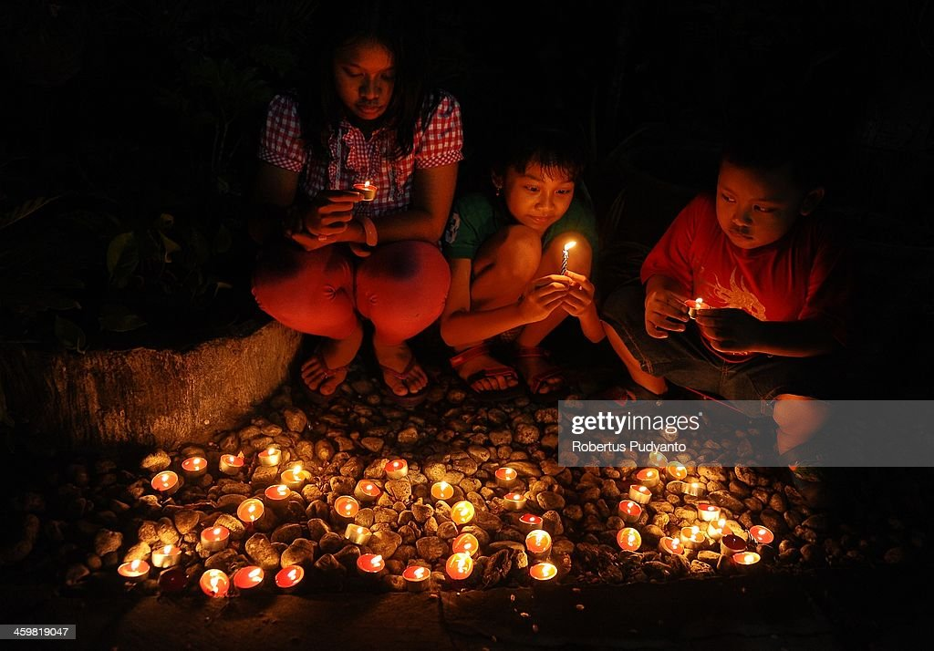 Young Indonesians lite candles and pray to celebrate 2014 New Years on December 31, 2013 in Surabaya, Indonesia. A wave of pyrotechnic displays kicked off New Years celebrations in major cities around the world.