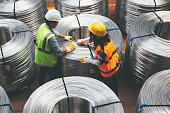 Young industry employees checking production line in wire warehouse