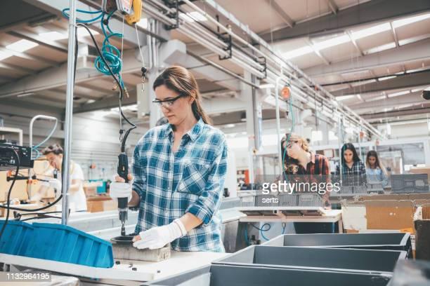 junge industrie-mitarbeiter arbeiten an der produktionslinie in der fabrik - fließbandfertigung stock-fotos und bilder