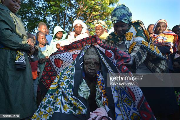 Young initiate receives colourful wrappers as a reward after succesfully undergoing a traditional circumcission rite at his village in Kenya's...