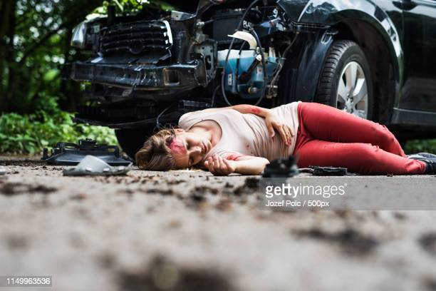 Young Injured Woman Lying On The Road After A Car Accident, Unconscious