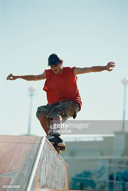 Young inline skater grinding the rail at a skate park