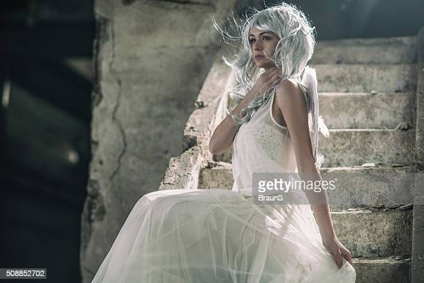 Young innocent angel sitting on stairs in a ruin.