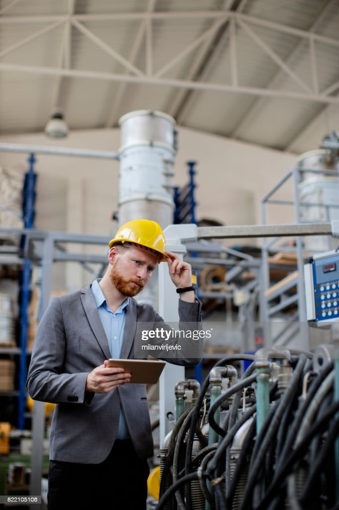 Young inspector in factory wearing yellow helmet : Stock Photo