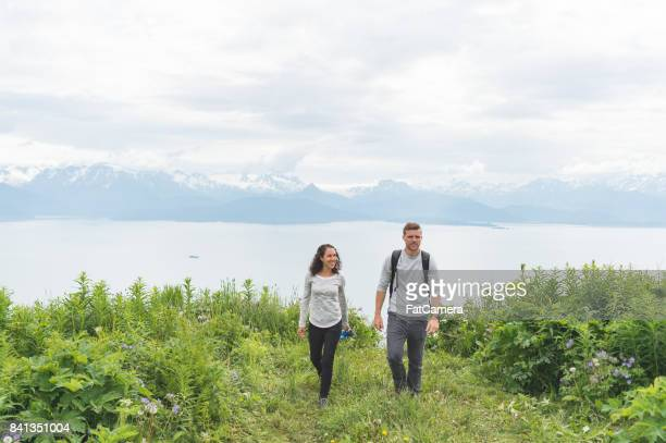 Young interracial couple hiking to an Alaskan viewpoint