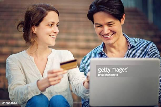 若い異人種間のカップルを使用してオンライン ショッピングのラップトップとクレジット カード