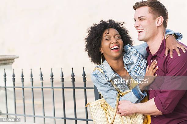 Young interracial couple laughing outdoors