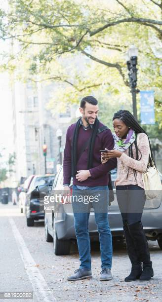 Young interracial couple waiting for car to pick them up