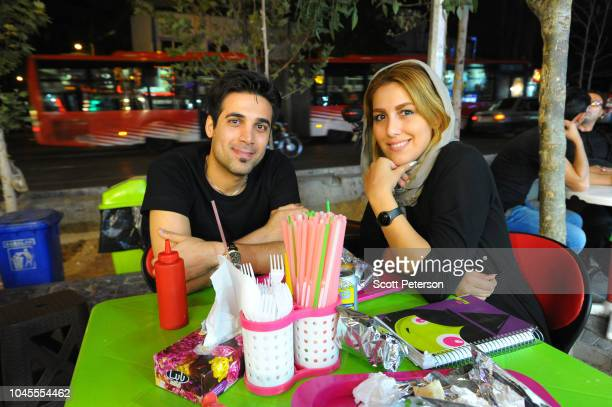 Young Iranian couple sit at a table on the sidewalk, as they wait to be served roast chicken from a street shop, as Iranians try to lead normal lives...