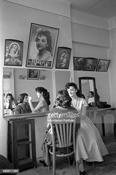 A young Iranian makeup woman putting make up on a young Itanian girl's face Tehran 1956