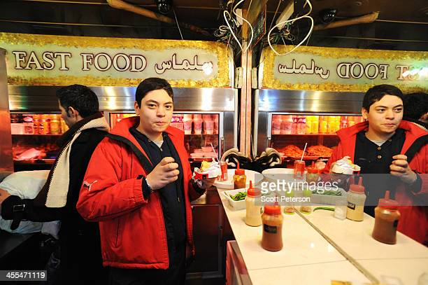 A young Iranian man eats at a fast food shwarma sandwich restaurant on December 9 2013 in Tehran Iran Iran's economy has been struck by years of...