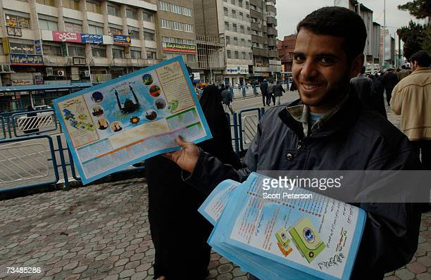 A young Iranian man hands out posters with the image of Jamkaran Mosque where some Shiite Muslims believe they can be close to the 12th Imam the...
