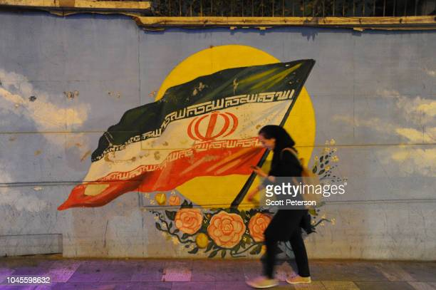 A young Iranian woman walks past an Iranian flag painted on a wall as Iranians try to lead normal lives while bracing for renewed US sanctions on...