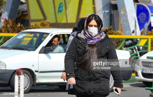 Young Iranian woman wearing a protective mask, crosses a busy street in the capital Tehran on February 22, 2020. - Iran today reported one more death...