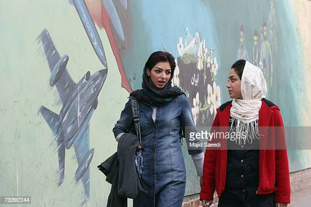 Young Iranian women walk past a mural on the wall of the former US embassy apparently undaunted by media reports of potential airstrikes by the US if...