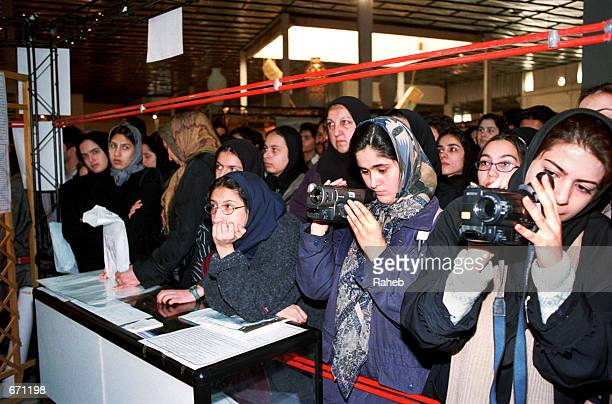 Young Iranian women watch a singer perform at a youth fair January 11 2001 in Tehran Iran The fair was organized by an aide to President Mohammad...
