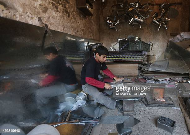 A young Iraqi boy cuts aluminium sheets at a workshop in a market in Baghdad on December 2 2014 The International Monetary Fund said in its October...
